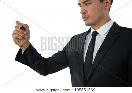 Young businessman writing on invisible interface against white background