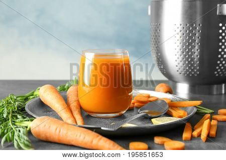 Composition with glass of homemade juice, lemon and carrot slices on metal plate