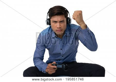 Businessman with fist wearing headphones while playing video game against white background