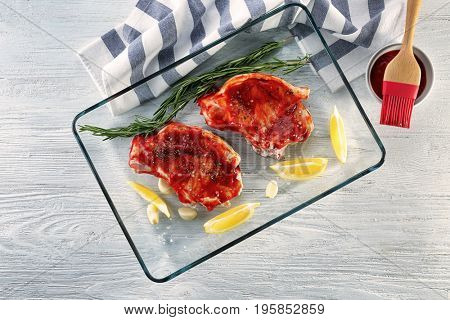 Pork ribs with tomato sauce and lemon slices in glass baking tray on table