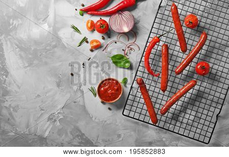 Composition with yummy sausages with sauce and vegetables on cooling grid