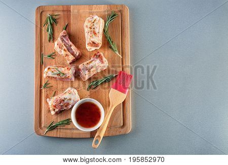 Wooden board with pork ribs, sauce and basting brush on table