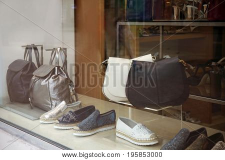 View through showcase on shoes and accessories in shop