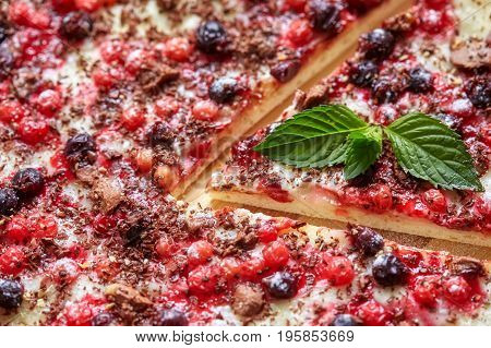 Piece of sweet pizza with currant redcurrant mint and chocolate closeup