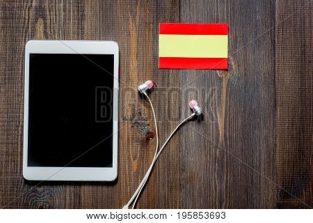 Self-development. Learning languages online. Headphones and tablet PC on wooden background top view.