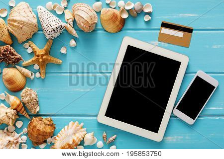 Summer online shopping on digital tablet, sea vacation background, seashells on blue wood