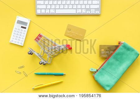 Shopping in online store. Bank card nearby keyboard, purse, shopping cart on yellow background top view.