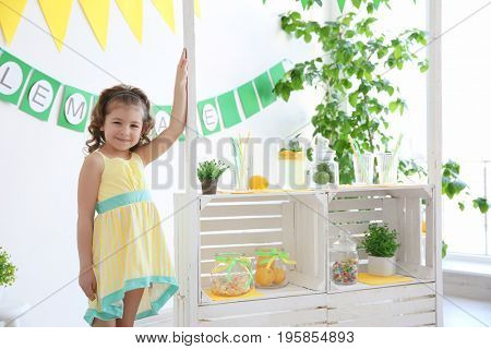 Cute little girl standing near stand with lemonade