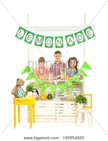 Cute little kids selling lemonade at counter on white background