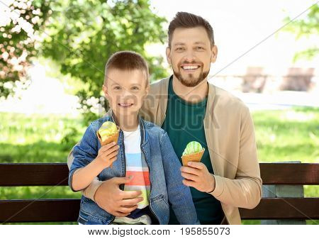 Dad and son eating ice cream on bench in the park on sunny day