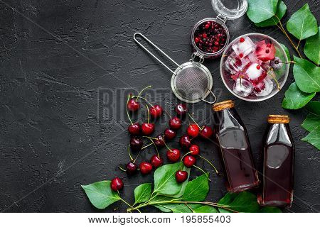 Summer ice berry juice with cherry and cranberry on black table top view.