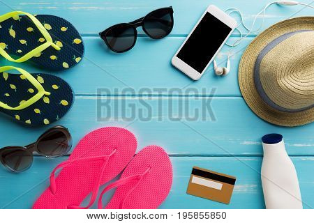 Vacation background on blue wood, top view with copy space. Flip flops, sunglasses and straw hat. Booking tickets online on smartphone.