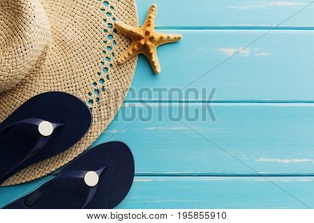 Vacation background on blue wood, top view with copy space. Beach pebbles, flip flops, seashell and straw hat