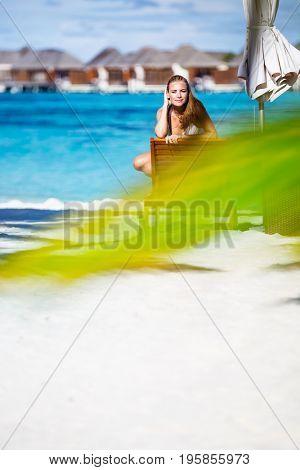 Beautiful woman on the beach, wearing white bikini and taking sun bath on the sunbed, photo with copy space, enjoying summer holidays on Maldive islands
