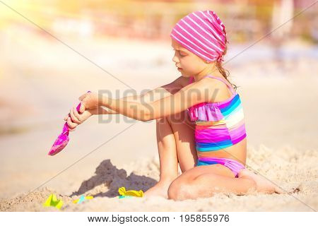 Little girl having fun on the beach, cute sweet baby wearing pink swimsuit and kerchief playing with sandbag and shovel, happy summer vacation