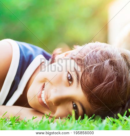 Closeup portrait of a happy smiling boy lying down on the fresh green grass in bright sunny day, enjoying summer holidays in countryside