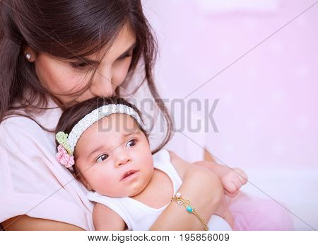 Closeup portrait of beautiful woman with gentleness kissing her cute newborn daughter, enjoying parenthood, mother's love concept