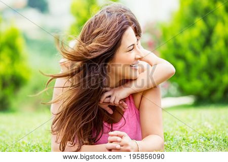 Happy mother with daughter lying down on fresh green grass field, joyful family with pleasure spending time together outdoors, enjoying summer holidays