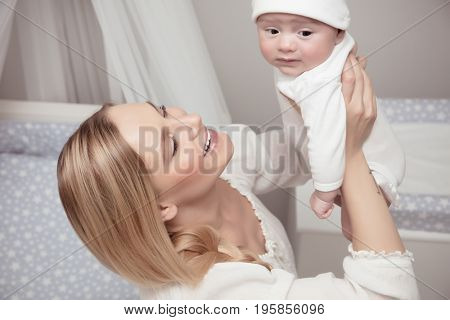 Portrait of a smiling mother with her precious baby spending time at home, enjoying parenting, happy family life