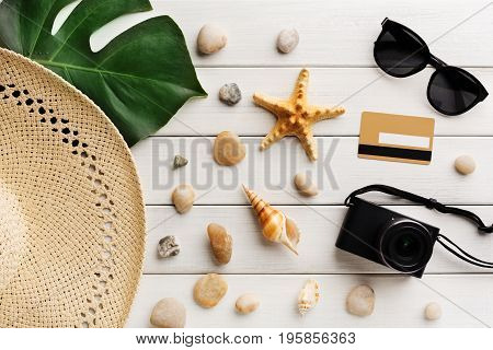 Vacation background on white wood, top view with copy space. Straw hat, sunglasses, credit card and seashells