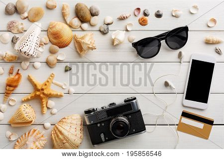 Vacation background on white wood, top view with copy space. Retro photo camera and sunglasses. Booking tickets online on smartphone.