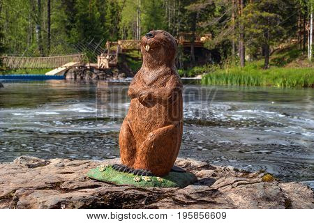 Ruskeala, Republic of Karelia, Russia - June 12, 2017: Smiling Bober is a wooden art composition near the Ahvenkoski waterfall on the Tomaioki River. The sculpture stands on the rocks in the middle of the dam surrounded by waterfalls.