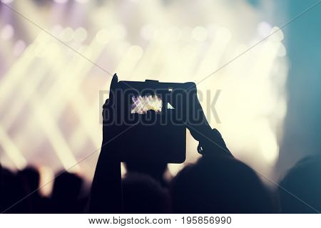 Silhouette of hands using camera phone to take pictures and videos at pop concert, festival.Retro styled photo.