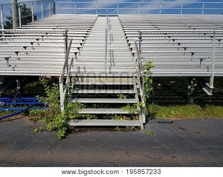 outdoor metal seating with weeds growing near the steps