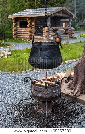 Water boils in the cauldron over an open fire. The soup will be cooked in the cauldron. The cauldron is black with soot. In the background, the house is made of logs.