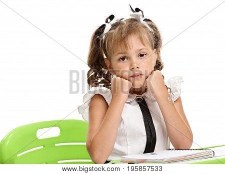 Portrait of sad little girl sitting on boring lesson
