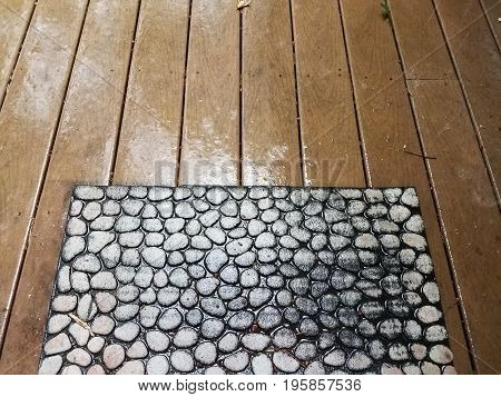 composite wood deck with water on it during a rain and welcome mat