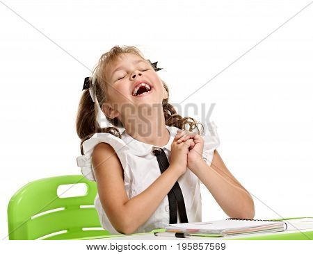 Excited happy little girl sitting at the desk and laughing