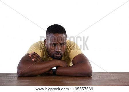 Upset man sitting at table against white background