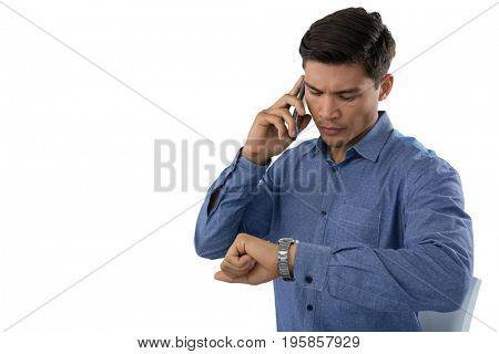 Businessman looking time while talking on smartphone against white background