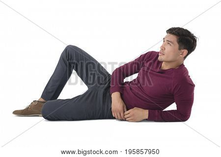 Full length of businessman looking away while reclining against white background