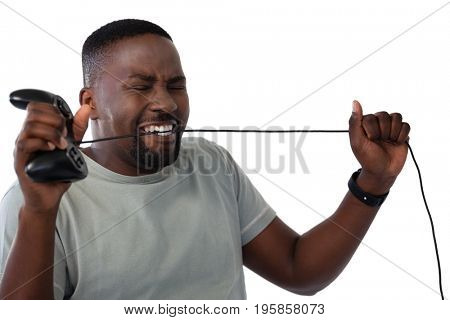 Frustrated man biting a wire of joystick against white background