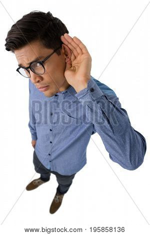 Portrait of businessman cupping ears while standing against white background