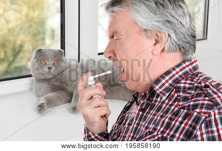 Senior ill man using throat spray and pet on background. Concept of allergies to cats