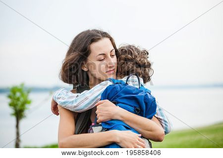 A Woman Is Hugging A Boy.