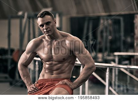 Portrait of handsome physically fit young man in fitness club, the image was desaturated ang toned
