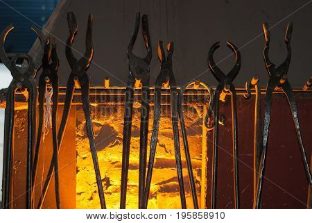 Set of old blacksmith tongs closeup, against horn, the light from the fire