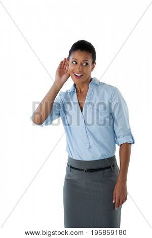 Smiling businesswoman listening secretly with hands behind her ears