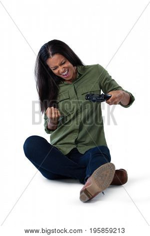 Excited woman playing video games against white background