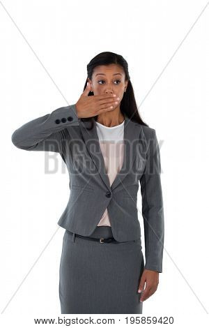 Surprised businesswoman covering her mouth with hand against white background