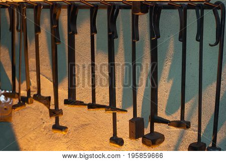 Set of hammers for forging on the wall in the smithy, the tools of a blacksmith