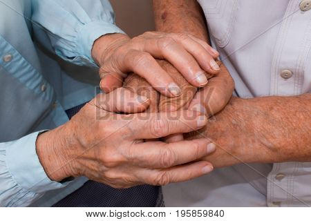 Hands of two loving senior people on a black background