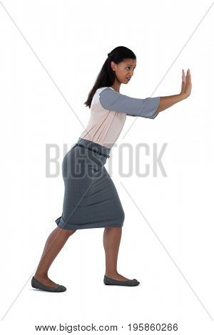 Side view of businesswoman pushing against white background