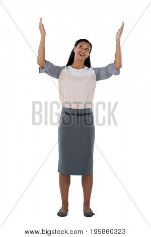 Businesswoman standing with hands raised against white background