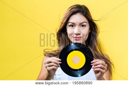 Happy young woman holding a record on a yellow background