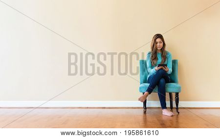 Young latina woman reading with an e-reader in a chair in a large interior room
